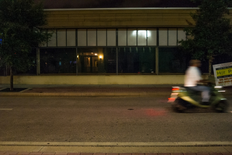 From the shadows comes a photo of a guy on his scooter.